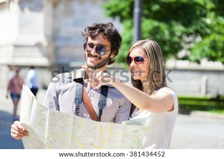 Young tourists reading a map - stock photo