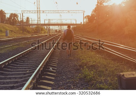 young traveler is going along the railway in sunset