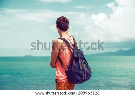 Young traveler man with backpack staying alone at seaside and looking to the ocean, exploring the world fell new emotions, vintage instagram colors, deep blue sky and sea water. - stock photo