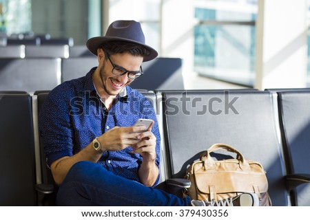 Young traveler on an airport, with a leather jacket laughing with his smartphone - stock photo