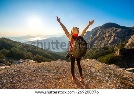 Young traveler photographer with photo camera and backpack standing on the top of mountain and looking on the sunset - stock photo
