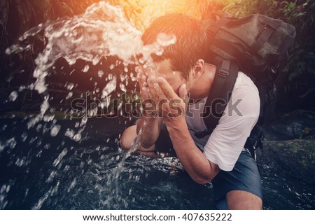 Young traveler washing his face in the wild river (intentional sun glare and motion blur) - stock photo