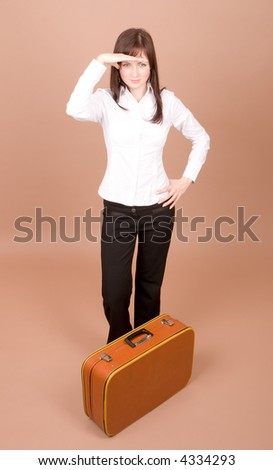 Young traveler with suitcase isolated on beige background