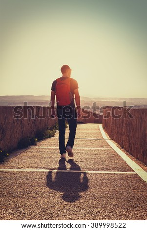 Young traveller with backpack walking by the road at sunset