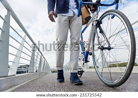 young trendy black african hipster man with bicycle walking in urban city on way commute to work - stock photo