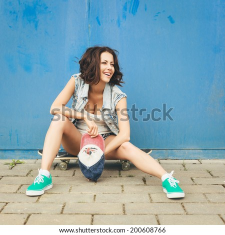 Young trendy girl in jacket sitting on a skateboard on the background of blue wall. Outdoor lifestyle portrait - stock photo