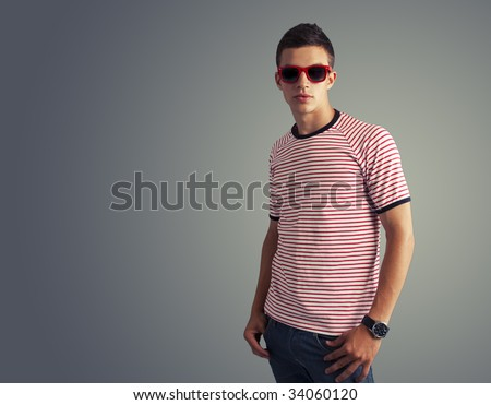 young trendy male model posing in studio - stock photo