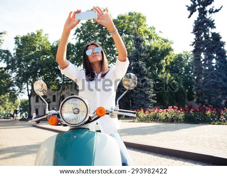 Young trendy woman making selfie photo on scooter in european town - stock photo