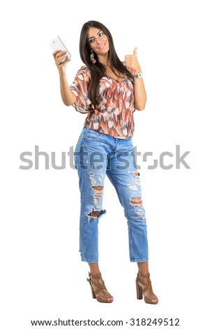 Young trendy woman taking selfie with thumbs up gesture. Full body length portrait isolated over white studio background.