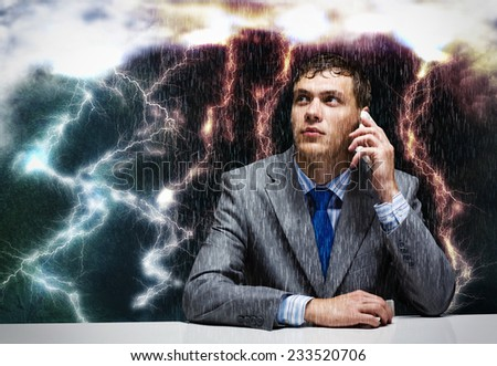 Young troubled businessman sitting under rain and talking on phone - stock photo