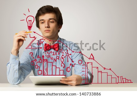 Young troubled man sitting at table with laptop - stock photo