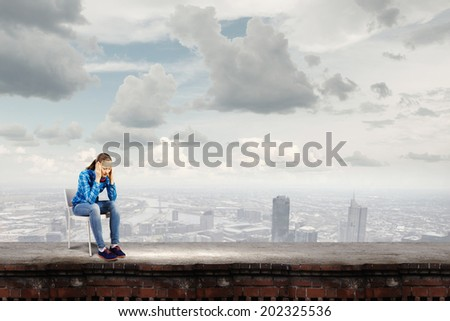 Young troubled woman sitting on chair on building top - stock photo
