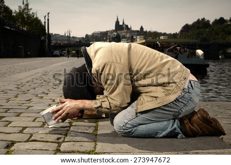 Young ugly beggar on his knees - stock photo