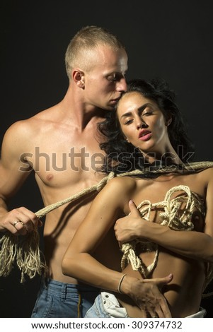 Young undressed pair of sexy pretty tan woman in jeans and man with strong muscular beautiful body with rope standing close to each other on black background, vertical picture - stock photo