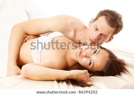 Young unhappy couple in bed - stock photo