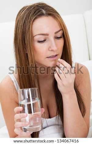 Young Unhappy Woman Holding Pills And Glass Of Water