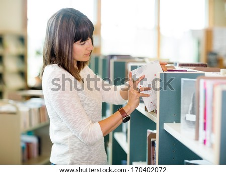 Young university student selecting books in bookstore - stock photo