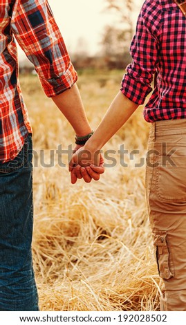 Young unrecognizable couple in love holding hands each other, serene scene - stock photo