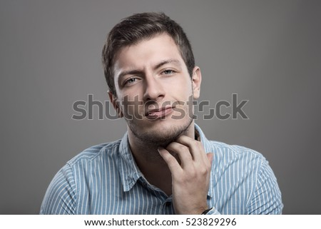 Young unshaven man scratching itchy beard with painful expression looking at camera