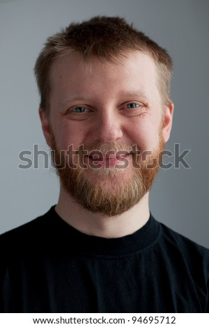 Young upbeat guy with a beard in  black T-shirt