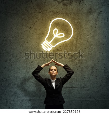 Young upset businesswoman and light bulb above head - stock photo