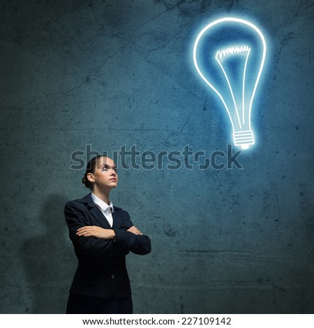 Young upset businesswoman looking at light bulb above head