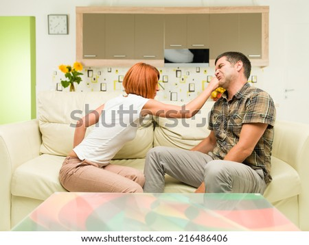 young upset caucasian woman sitting on sofa, punching man sitting next to her