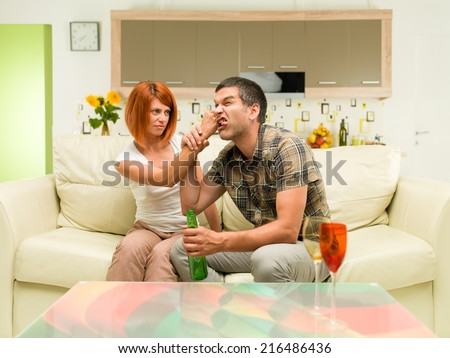 young upset caucasian woman sitting on sofa, punching man sitting next to her - stock photo