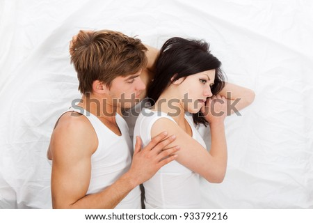 young upset couple lying in a bed, having problem. Divorce and separation conflict sad looking at camera, negative emotions concept, top view - stock photo