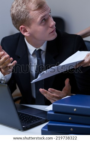 Young upset employee arguing with his boss at the office