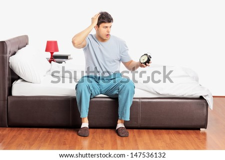 Young upset male sitting on a bed, holding an alarm clock and gesturing late - stock photo