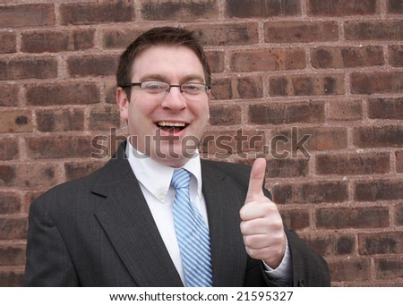 Young urban businessman giving a thumbs up - stock photo