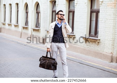 Young urban businessman on smart phone running in street talking on smartphone smiling wearing jacket and leather bag - stock photo