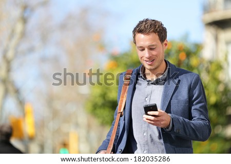 Young urban businessman professional on smartphone walking in street using app texting sms message on smartphone wearing jacket on Passeig de Gracia, Barcelona, Catalonia, Spain. - stock photo