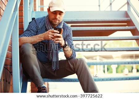 Young urban businessman professional on smartphone walking in street using app texting sms message on smartphone  - stock photo