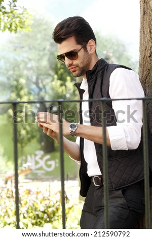 Young urban businessman standing in park. Business people.  - stock photo