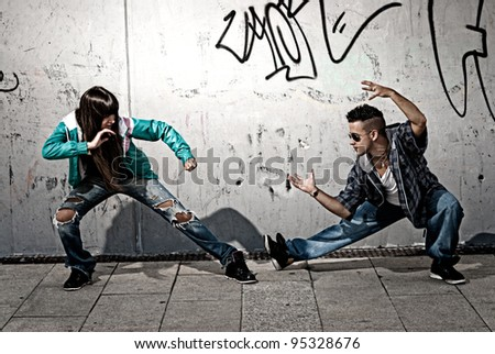 Young urban couple dancers hip hop dancing fight acting urban scene - stock photo