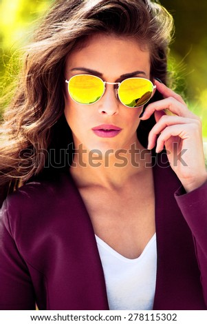 young urban fashion woman wearing yellow sunglasses and purple jacket, outdoor shot in the city - stock photo