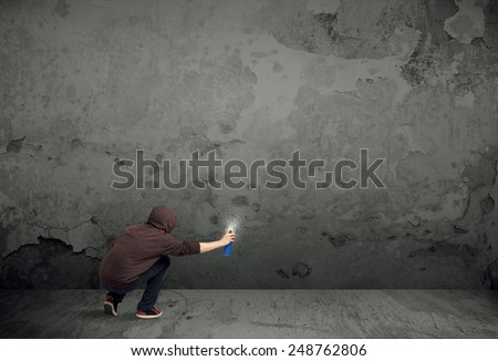 Young urban painter starting to draw graffiti on the wall  - stock photo