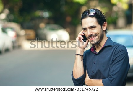 Young urban professional man using smart phone. Businessman talking on a phone while waiting to cross the street - stock photo