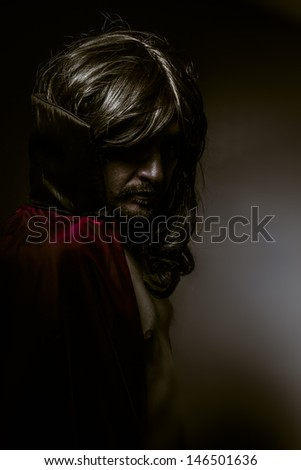 Young Vampire with black coat and long hair, nude - stock photo