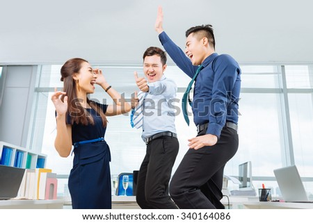 Young Vietnamese business colleagues dancing in the office - stock photo