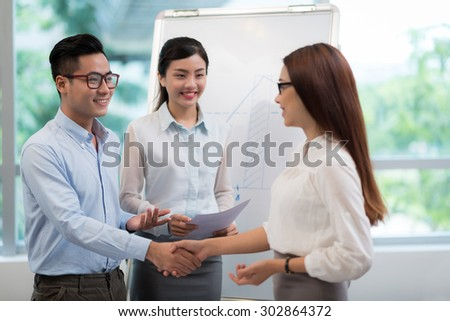 Young Vietnamese businessman greeting his female colleague