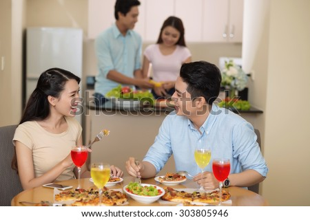 Young Vietnamese couple chatting and eating pizza at the party