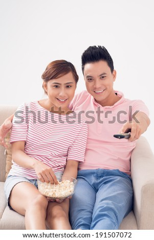 Young Vietnamese couple watching tv at home - stock photo