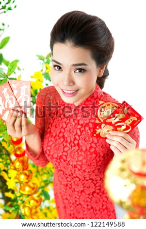 Young Vietnamese girl showing red envelopes with money for Tet
