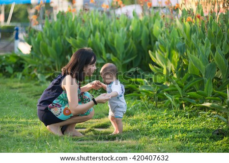Young Vietnamese mother help her son start walking. Mother teach her son, bring up, take care him. - stock photo