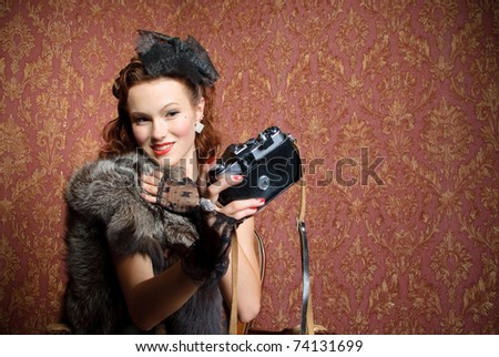 young vintage woman with camera in old-style studio - stock photo