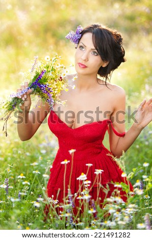 Young voluptuous brunette holding a wild flowers bouquet in a sunny day. Portrait of beautiful woman with low-cut red dress posing, outdoor shot. Provocative female enjoying the nature - stock photo