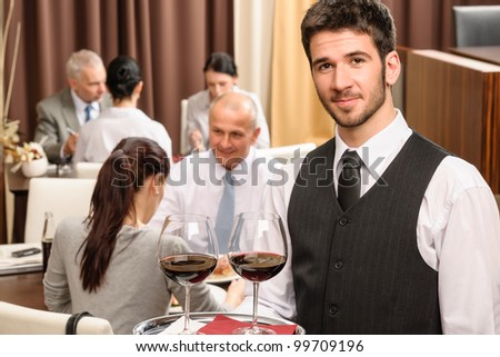Young waiter hold red wine business lunch at professional restaurant - stock photo